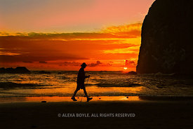 Hiker walks at sunset hour along the Pacific shore; Cannon Beach, Oregon, U.S.A.