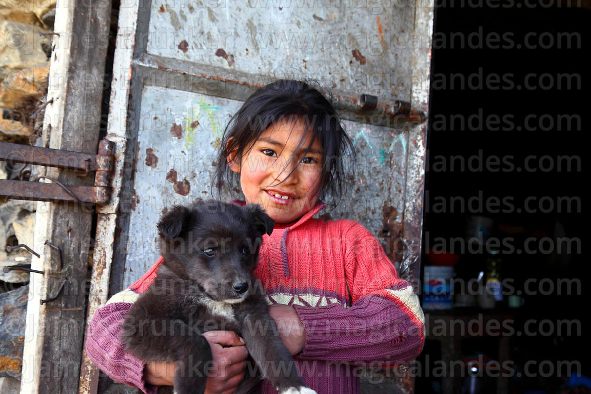 Young Quechua girl holding puppy outside her house, Abra Malaga, Peru