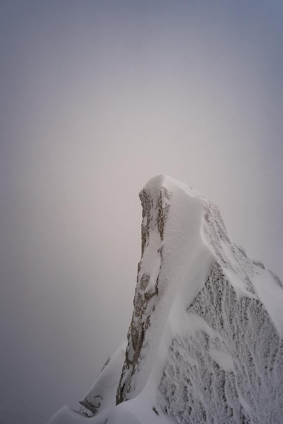 A snow and ice-covered jagged mountain summit in the French Alps. Photo by Jason Tinacci