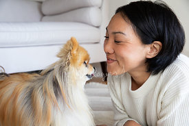 Young Asian Woman Smiles at a Senior Pomeranian Dog