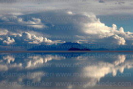 Storm clouds  reflected in  water on Salar de Uyuni in rainy season, Bolivia