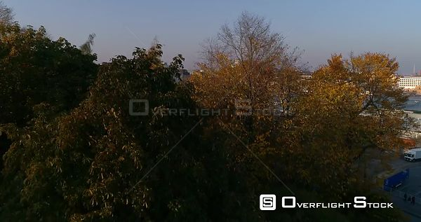 Autumn cityscape, C4K aerial, rising, drone shot, over ruska foliage and fall color trees, revealing Helsinki south harbor an...