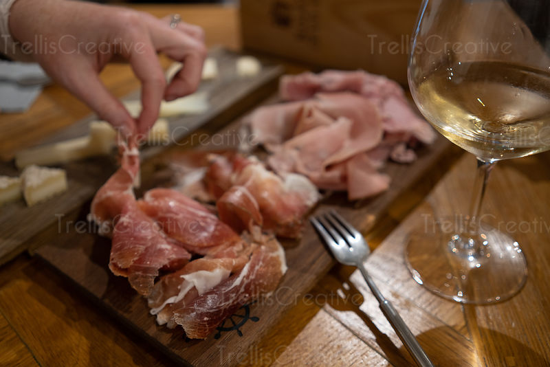 Woman's hand picking food from a charcuterie and cheese boards paired with white wines in a bistro, Lyon, France