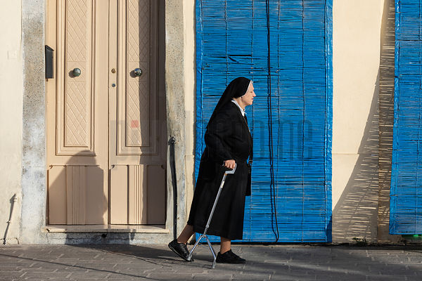 A Nun with a Walking Cane against a Blue Screen