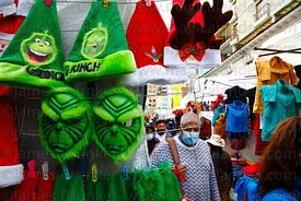 Man wearing face mask walking past street stall selling The Grinch hats and masks, La Paz, Bolivia