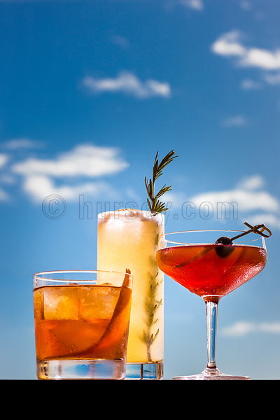 Photo of three cocktails shot against a blue sky