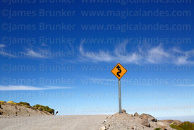 Sharp bends sign next to dirt road, Lauca National Park, Region XV, Chile