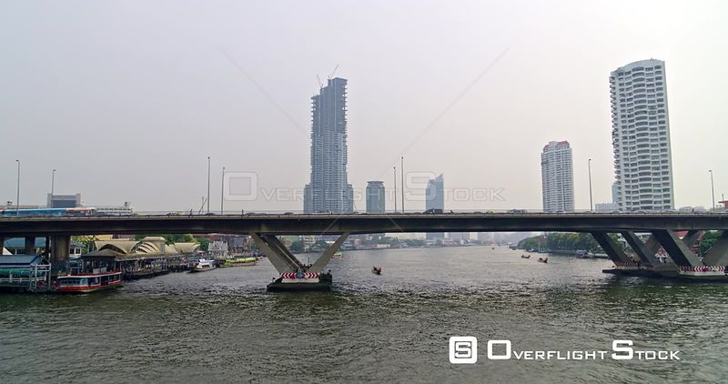 Thailand Bangkok Aerial Flying low over river with waterfront views and bridge detail