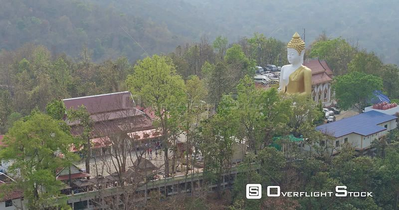 Chang Mai Thailand Aerial Birdseye peek at temple to flying away, in reverse, front temple view