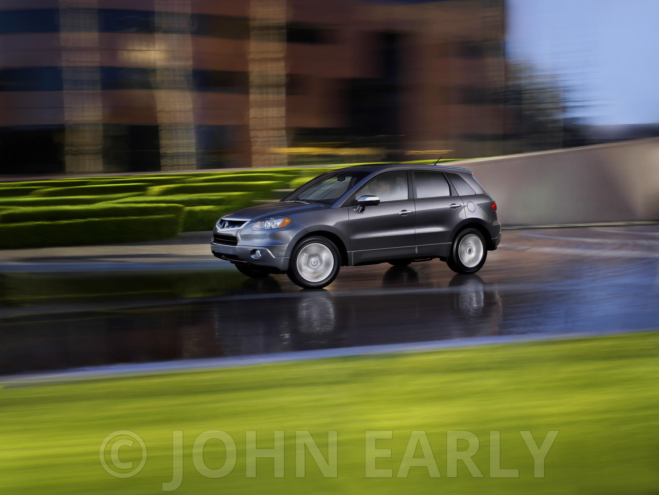 Grey SUV Driving Action 3/4 Front With  Business Park Background