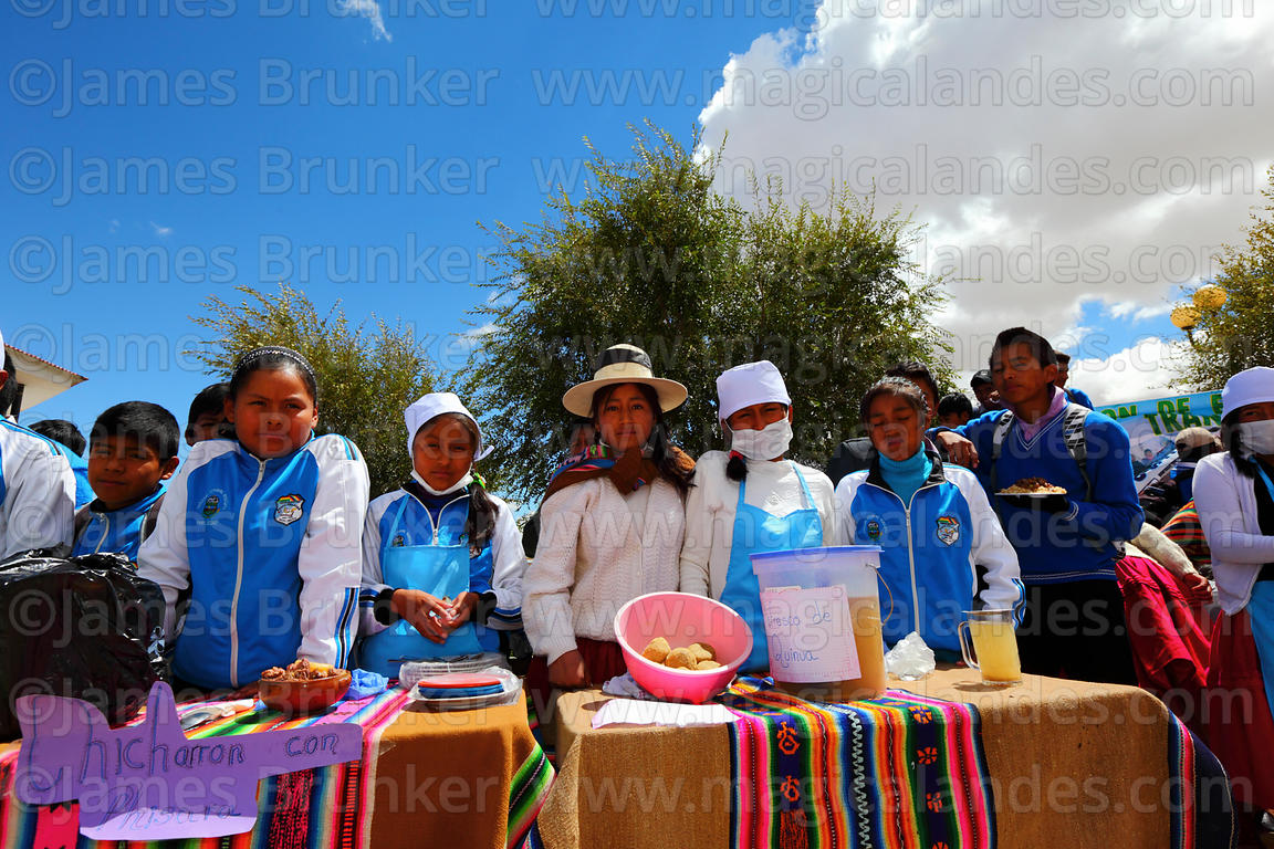 Students at stall with quinoa based soft drink and produce at an event to promote quinoa products, Pampa Aullagas, Bolivia
