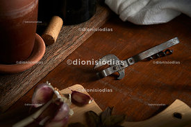 Antique tin opener on rustic wooden table between spices and bottles.