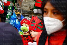 A girl wearing a face mask walks past a stall selling face masks (including one with The Grinch on it) in a Christmas market,...