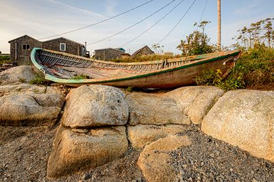 Old abandoned fishing boat on shore on Peggy's Cove, Nova Scotia