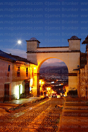 Full moon rising above archway at top of Cuesta Santa Ana street at twilight, Cusco, Peru
