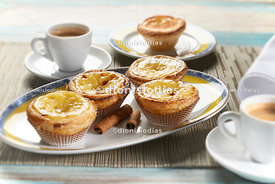 Belem pasteis on a platter with coffee cup in the background