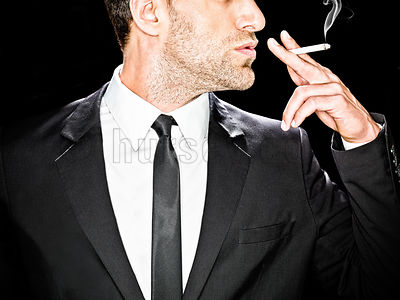 image of a male in a black suit against a black background smoking a cigarette, cropped at nose and chest body facing camera,...