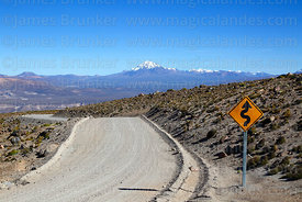 Sharp bends sign next to dirt road, Tacora volcano in distance, Lauca National Park, Region XV, Chile