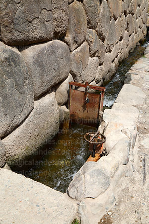 Modern sluice gate controlling water flow in Inca water channel next to street, Ollantaytambo, Sacred Valley, Peru