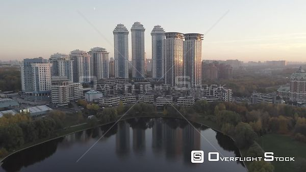 Autumn Sunset Backward Flying Over the Pond Towards Modern Residential Buildings. Moscow Russia Drone Video View