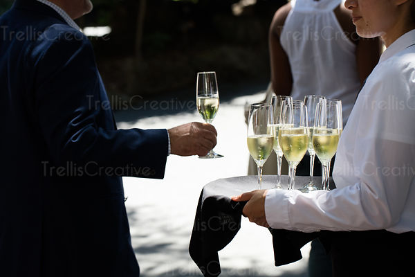 Guest taking a glass of champagne from a tray at a formal celebration.
