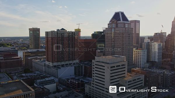 Baltimore Maryland Aerial Flying toward inner harbor next to downtown highrise cityscape with sun rays