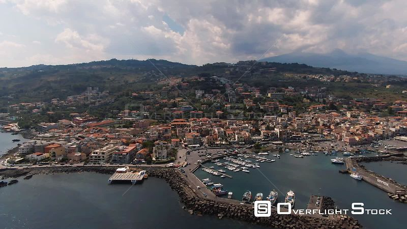 Aerial descending view of the fishing village of Aci Trezza in Sicily, with mount Etna in the background. Italy