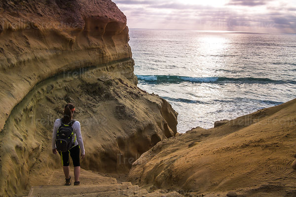 A young woman hikes down cliffs towards the sea, Torrey Pines State Preserve, California, USA.