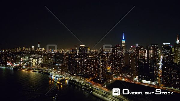 NYC New York Low to high nighttime cityscape moving over East River into Midtown Manhattan with FDR traffic