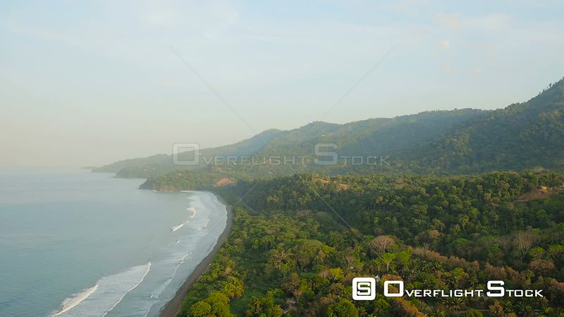 Flying over coastline beach and panning towards jungle forest hills. Costa Rica