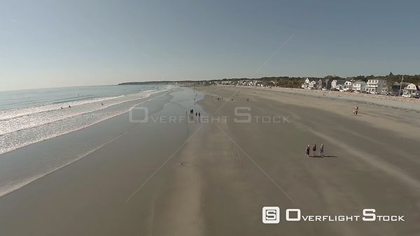 York, Maine beach low flying aerial over people and shoreline.
