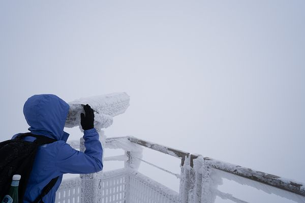 Tourist looks through ice covered binoculars into a foggy abyss. Photo by Jason Tinacci