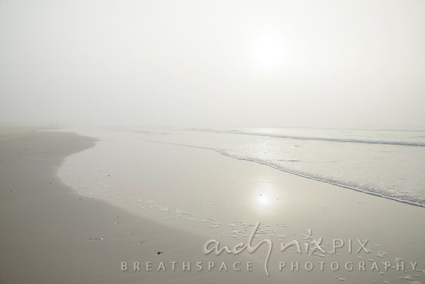 Pale sun on a misty morning reflects on the sea