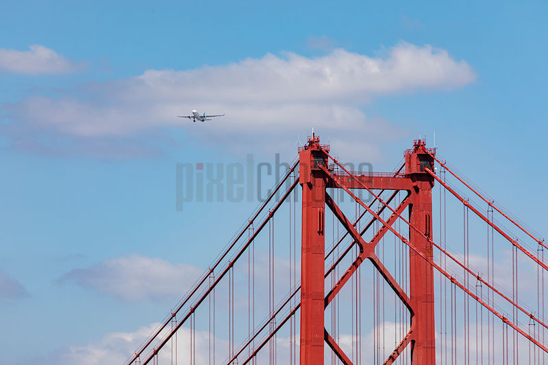 An Aeroplane takes off from Lisbon International Airport with he Ponte 25 de Abril Suspension Bridge in the Foreground