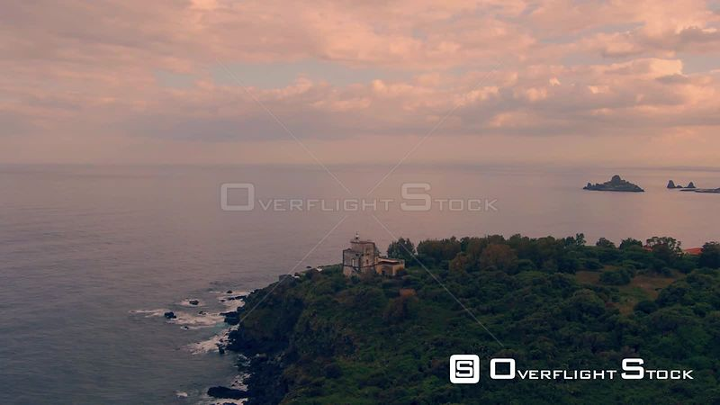 Aerial orbiting view of a lighthouse at sunset in the East coast of Sicily. Italy