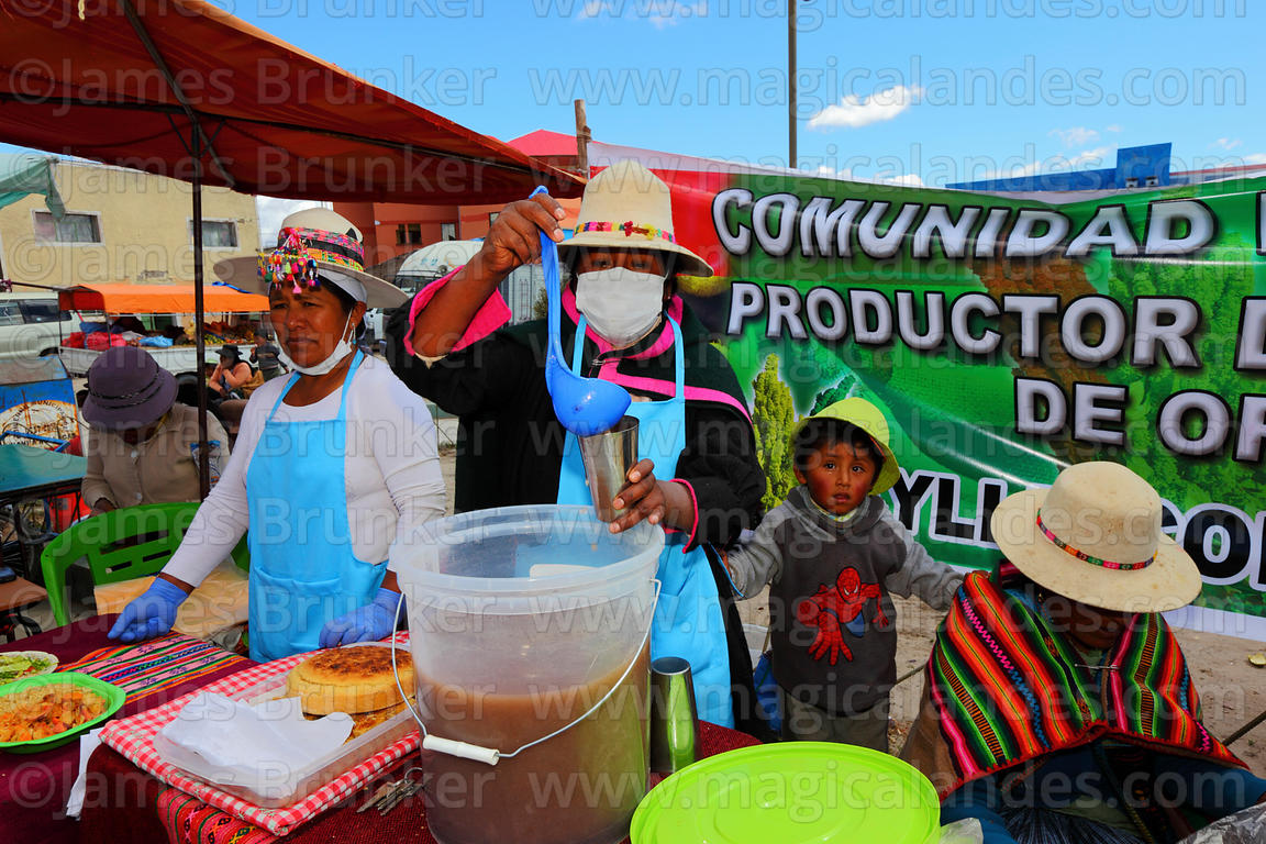 Aymara woman and girl at stall with quinoa based soft drinks at an event to promote quinoa products, Pampa Aullagas, Bolivia