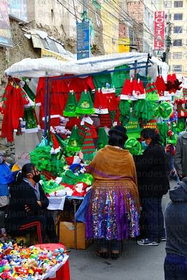 Aymara woman or cholita wearing traditional dress shopping at street stall selling Father Christmas and Grinch hats and costu...