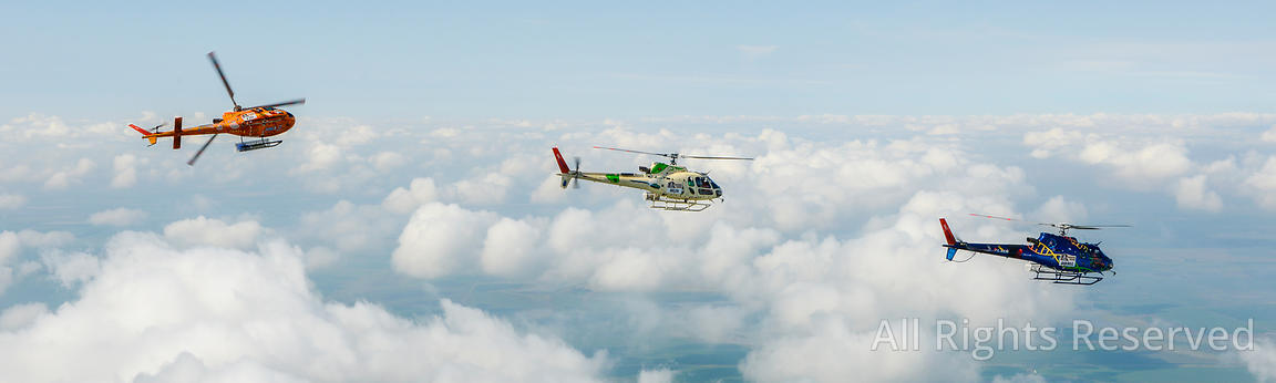 Air to Air Panorama Photo of Three Colorful Airbus Helicopters As350 B3 Ecureuil (squirrel Astar) Flying Above the Clouds and...