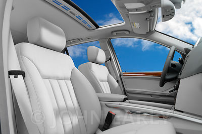 White Leather Car Interior With View of Blue Sky Through Sunroof and Windows