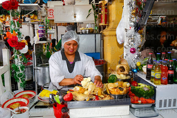 Woman with ingredients for caldo de gallina on stall in San Pedro market, Cusco, Peru