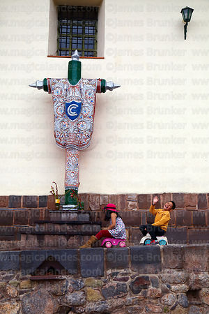 Children riding toy cars past cruz velakuy cross next to Santa Ana church, Cusco, Peru