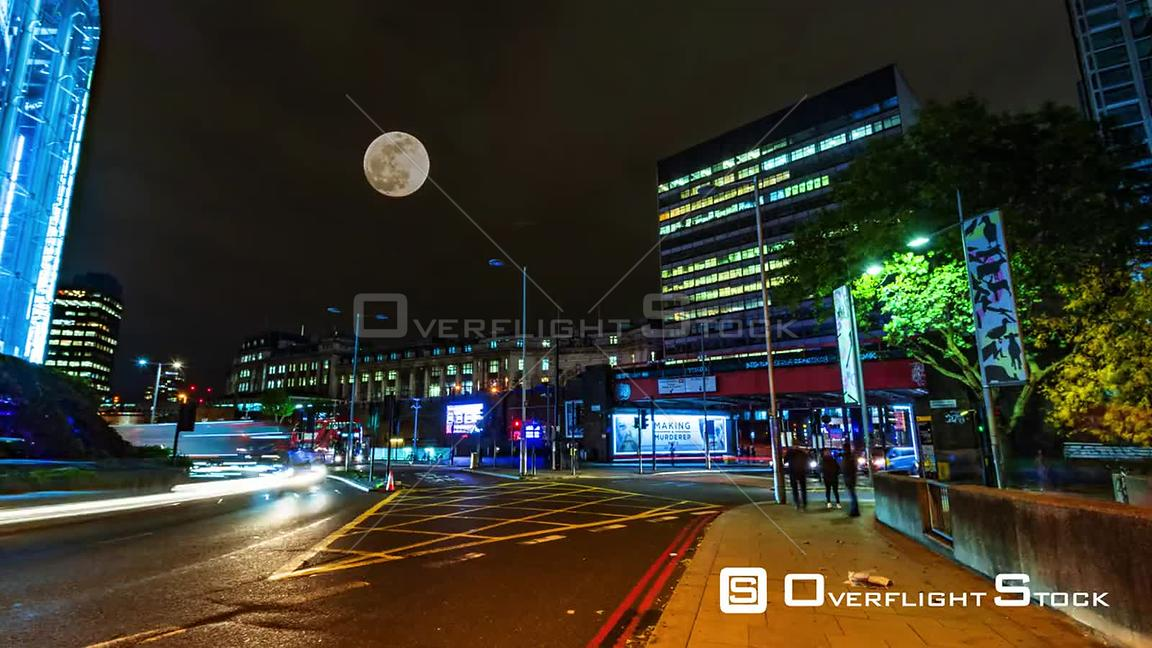 Timelapse view of a busy crossroad near Waterloo station in London at night with full moon