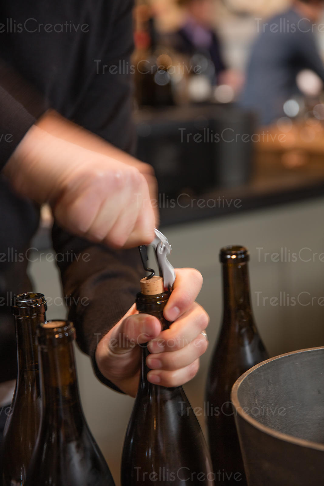 Sommelier opening a bottle wine with corkscrew.