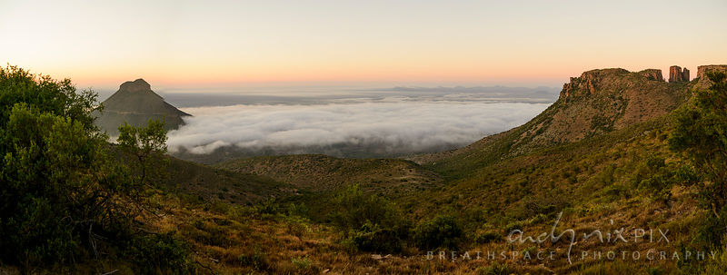 Elevated panoramic view of low mist clouds covering the Plains of Camdeboo in the Karoo Desert, with the escaprpment rising a...