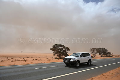 Vehicle travels on Sturt Highway, during drought.