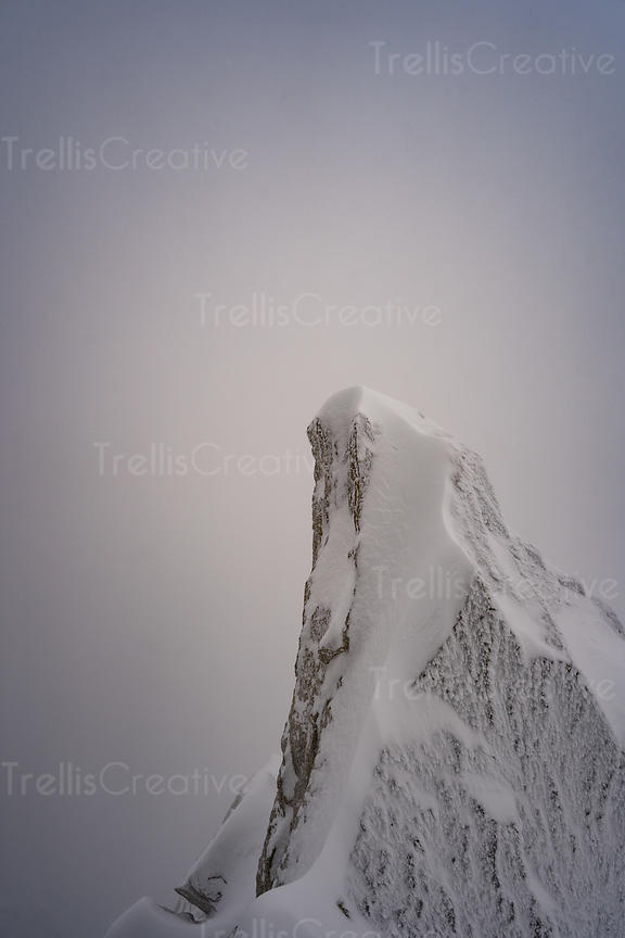 A snow and ice-covered jagged mountain summit in the French Alps