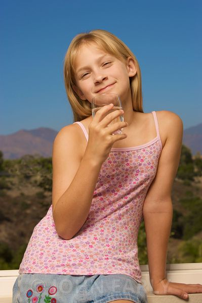 Young girl drinking clean clear water out of a glass