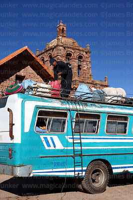 Driver loading luggage onto roof of local bus in front of of San Pedro church, Tiwanaku, La Paz Department, Bolivia