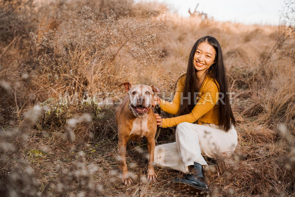 Large Smiling Senior Dog With Woman in Field Looking at Camera