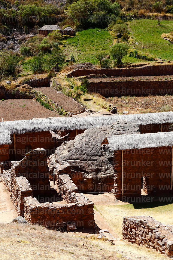 View of buildings around the large boulder or huaca at Inca site of Urco / Urqo, near Calca, Cusco Region, Peru